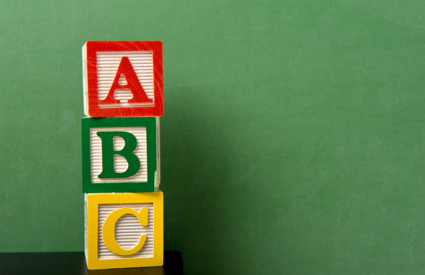 ABC blocks in front of a green chalkboard with copy space