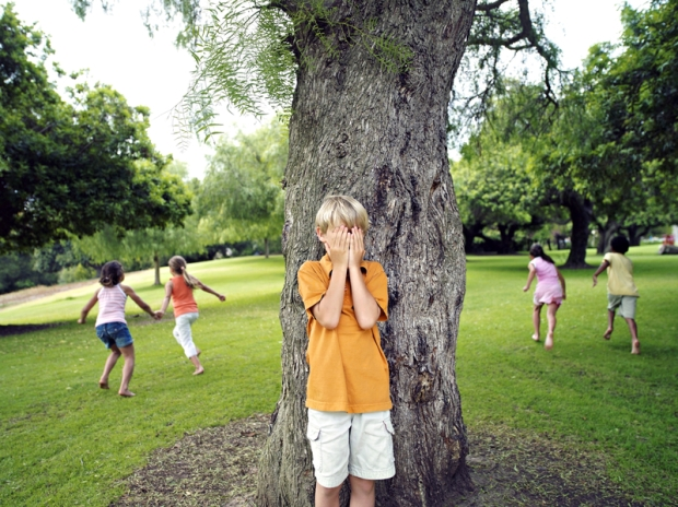 Boy with hands covering eyes playing hide and seek