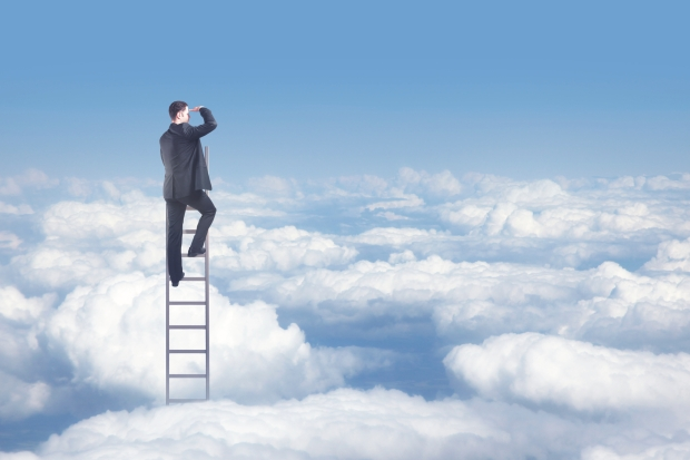 A businessman climbing the ladder to the top
