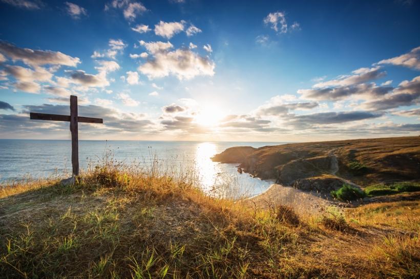Christian cross on a wild beach with a wonderful sunrise