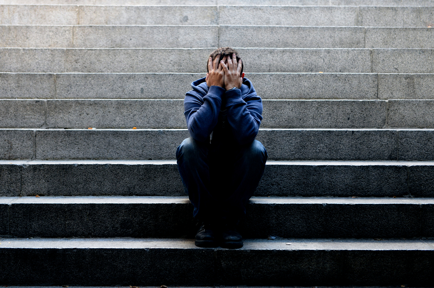 Young man suffering depression sitting on ground street concrete stairs