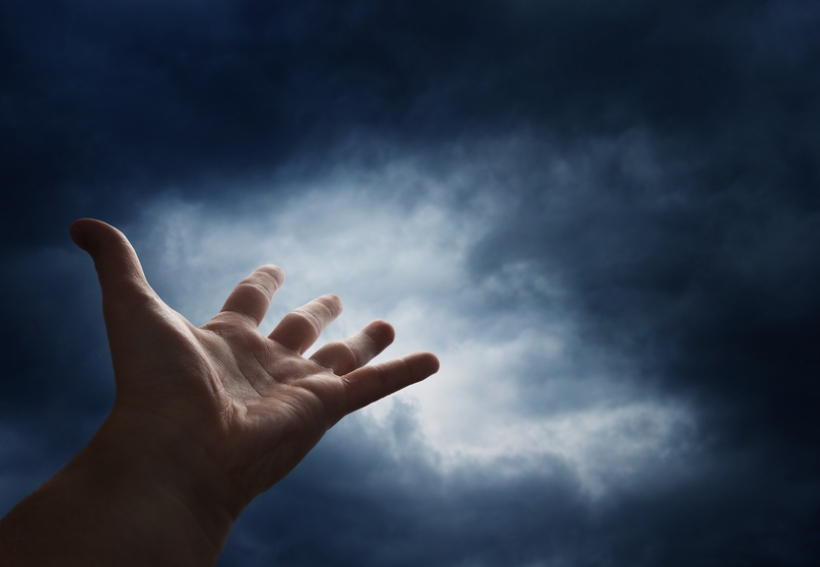 Hand reaching for the cloud in the sky