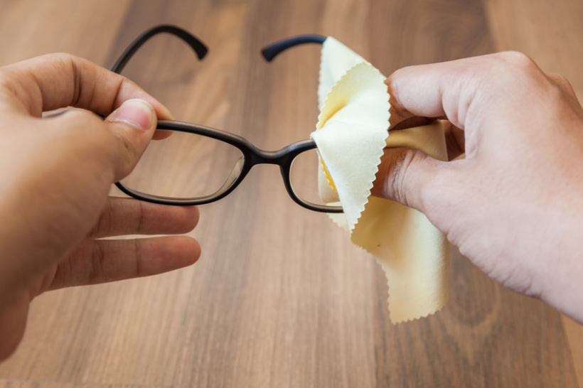 both hand cleaning glasses with cloth