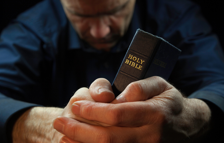 A man with his head bowed and holding a holy bible in prayer