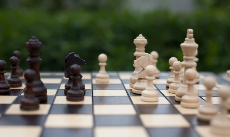 knights, pawns and other wooden chess pieces on the chessboard